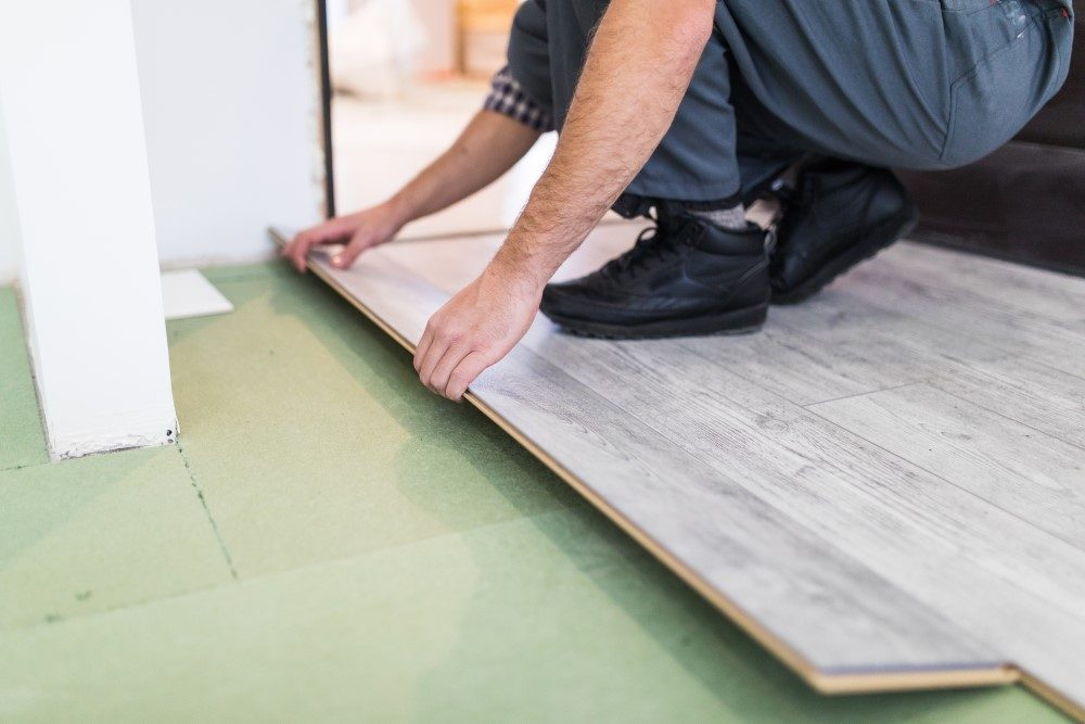 worker processing floor with laminate flooring boards